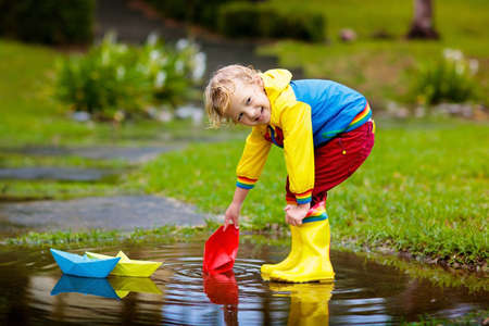 Niño con barco de papel en charco. Niños por la lluvia. Foto de archivo