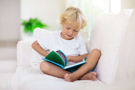 Child reading book. Kids read books. Little boy sitting on white couch in sunny living room watching pictures in story book. Kid doing homework for elementary school or kindergarten. Children study. Stockfoto