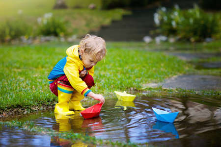 Child playing with paper boat in puddle. Kids play outdoor by autumn rain. Fall rainy weather outdoors activity for young children. Kid jumping in muddy puddles. Waterproof jacket and boots for baby. Foto de archivo - 126112540
