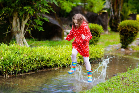Child playing in puddle. Kids play and jump outdoor by autumn rain. Fall rainy weather outdoors activity for young children. Kid jumping in muddy puddles. Waterproof jacket and boots for little girl. Banque d'images - 126112542