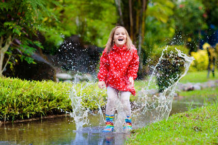 Child playing in puddle. Kids play and jump outdoor by autumn rain. Fall rainy weather outdoors activity for young children. Kid jumping in muddy puddles. Waterproof jacket and boots for little girl.