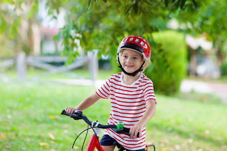 Kids on bike in park. Children going to school wearing safe bicycle helmets. Little boy biking on sunny summer day. Active healthy outdoor sport for young child. Fun activity for kid.