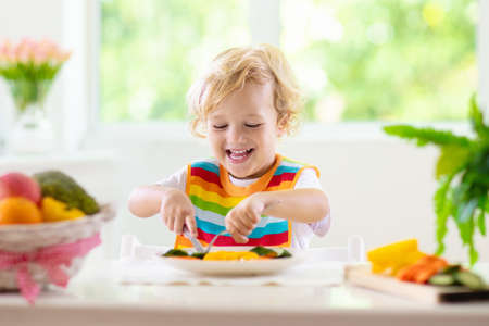 Child eating vegetables sitting in white high chair. Solid food for baby. Little boy eating healthy vegetable lunch of steam cooked carrots. Nutrition for toddler and preschooler. Kids eat fruit.