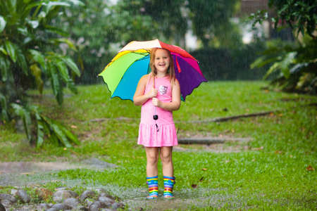 Bambino che gioca sotto la pioggia. I bambini con ombrello e stivali da pioggia giocano all'aperto sotto la pioggia battente. Bambina che salta nella pozzanghera fangosa. I bambini si divertono con il tempo piovoso autunnale. Bambino in esecuzione in tempesta tropicale.