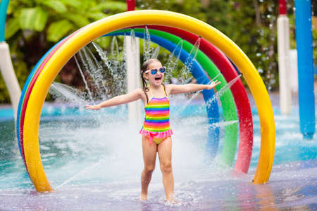 Kids play in aqua park. Children at water playground of tropical amusement park. Little girl at swimming pool. Child playing at water slide on summer vacation in Asia. Swim wear for young kid. Stock Photo - 126191583