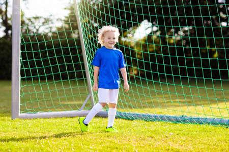 Los niños juegan al fútbol en el campo al aire libre. Los niños marcan un gol durante el partido de fútbol. Niño pateando la pelota. Niño corriendo en camiseta del equipo y tacos. Club de fútbol escolar. Entrenamiento deportivo para jugadores jóvenes. Foto de archivo