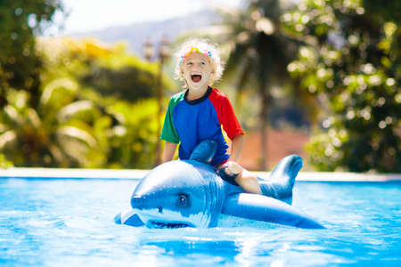 Child playing in swimming pool. Kids learn to swim. Little baby boy with inflatable toy float playing in water on summer vacation in tropical resort. Kid with toy shark on beach holiday.