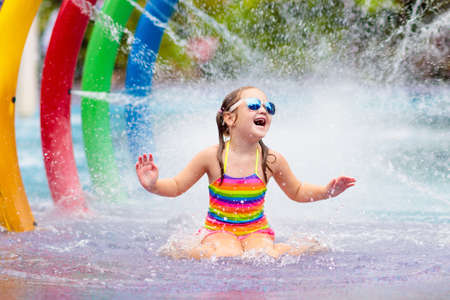 Kids play in aqua park. Children at water playground of tropical amusement park. Little girl at swimming pool. Child playing at water slide on summer vacation in Asia. Swim wear for young kid. Stock Photo - 126191592
