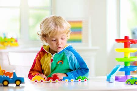 Kleiner Junge, der Spielzeugautos spielt. Junges Kind mit buntem Lernfahrzeug und Transportspielzeug. Kind, das Auto zum Regenbogenparkhaus fährt Kinder zu Hause oder in der Kita. Kindergarten- oder Vorschulspiel. Standard-Bild