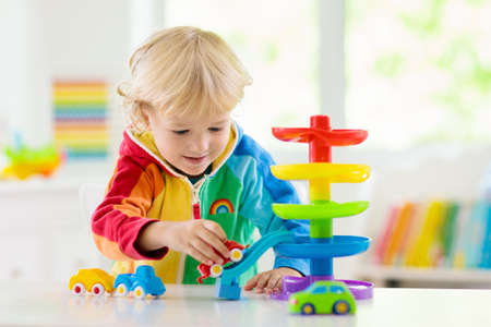 Little boy playing toy cars. Young kid with colorful educational vehicle and transport toys. Child driving car to rainbow parking garage. Kids at home or daycare. Kindergarten or preschool game. Stock Photo