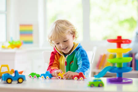 Little boy playing toy cars. Young kid with colorful educational vehicle and transport toys. Child driving car to rainbow parking garage. Kids at home or daycare. Kindergarten or preschool game. Stockfoto