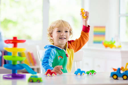 Mały chłopiec bawi się samochodzikami. Młody dzieciak z kolorowymi zabawkami edukacyjnymi pojazdu i transportu. Dziecko jazdy samochodem do garażu tęczy. Dzieci w domu lub przedszkolu. Gra przedszkolna lub przedszkolna.