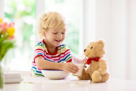 Niño desayunando. Niño que alimenta el juguete del oso de peluche, bebe leche y come cereal con fruta. Niño en la mesa de comedor blanca en la cocina en la ventana. Los niños comen. Nutrición saludable para niños pequeños. Foto de archivo