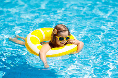 Child in swimming pool on inflatable yellow lemon ring. Little girl learning to swim with orange float. Water toy for baby and toddler. Healthy outdoor sport activity for children. Kids beach fun. Imagens