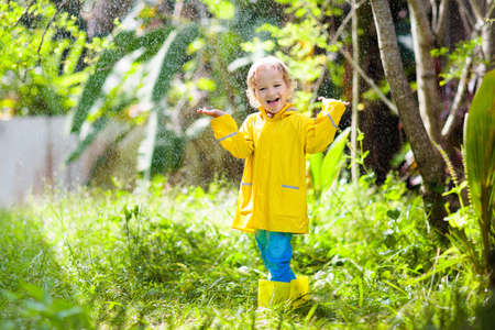Child playing in the rain on sunny autumn day. Kid under heavy shower with yellow duck umbrella. Little boy with duckling waterproof shoes. Rubber wellies boots. Fall outdoor activity by rainy weather Stock Photo