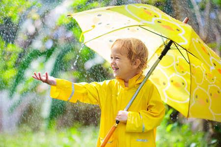 Bambino che gioca sotto la pioggia nella soleggiata giornata autunnale. Bambino sotto la doccia pesante con l'ombrello giallo dell'anatra. Ragazzino con scarpe impermeabili anatroccolo. Stivali di gomma. Attività all'aperto autunnale in caso di pioggia