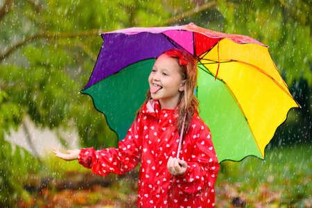 Kind, das im Regen im Herbstpark spielt Kind mit Regenschirm und Regenstiefeln spielt bei starkem Regen im Freien. Kleines Mädchen in roter Jacke unter Herbstdusche. Kinderspaß bei Regenwetter. Kinder spielen im Sturm.