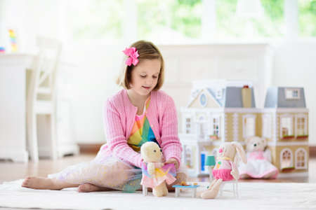 Little girl playing with doll house in white sunny bedroom. Kid with toys. Role game for young children. Child with teddy bear toy. Kids play tea party with stuffed animals and dolls. Nursery interior Foto de archivo - 127875265