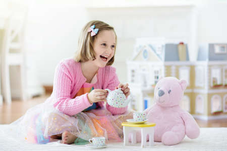 Little girl playing with doll house in white sunny bedroom. Kid with toys. Role game for young children. Child with teddy bear toy. Kids play tea party with stuffed animals and dolls. Nursery interior Foto de archivo - 127875271