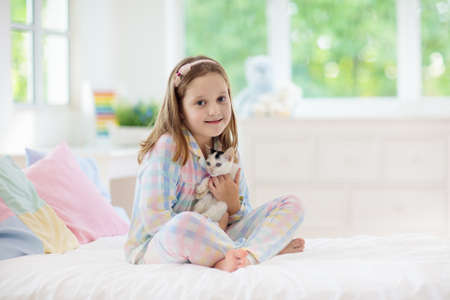 Child playing with baby cat on bed in white bedroom. Kid holding white kitten. Little girl in pajamas with cute pet animal at home. Kids play with cats. Children and domestic animals pets. Stockfoto