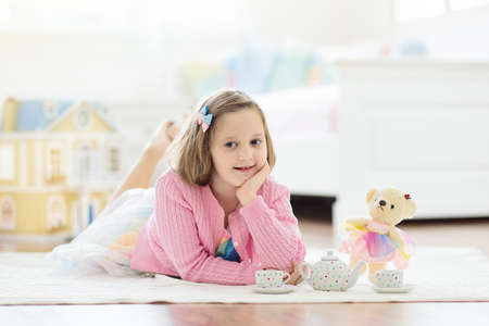 Little girl playing with doll house in white sunny bedroom. Kid with toys. Role game for young children. Child with teddy bear toy. Kids play tea party with stuffed animals and dolls. Nursery interior Foto de archivo - 127875270