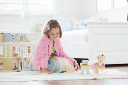 Little girl playing with doll house in white sunny bedroom. Kid with toys. Role game for young children. Child with teddy bear toy. Kids play tea party with stuffed animals and dolls. Nursery interior Foto de archivo - 127875279
