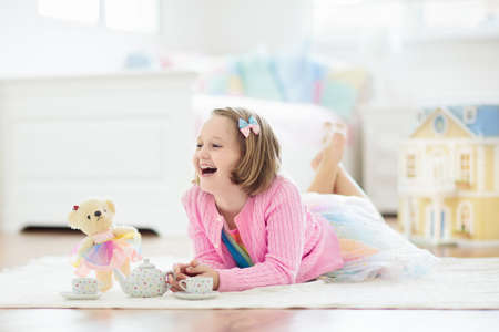Little girl playing with doll house in white sunny bedroom. Kid with toys. Role game for young children. Child with teddy bear toy. Kids play tea party with stuffed animals and dolls. Nursery interior Foto de archivo - 127875284