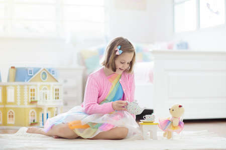 Little girl playing with doll house in white sunny bedroom. Kid with toys. Role game for young children. Child with teddy bear toy. Kids play tea party with stuffed animals and dolls. Nursery interior Foto de archivo - 127875289