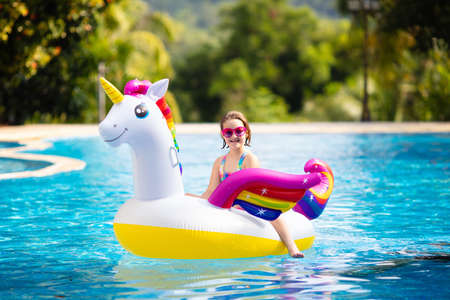 Child on unicorn float in swimming pool of tropical resort. Kids swim and play with inflatable water toys. Little girl playing on pink pony ring on family summer vacation on exotic island. Beach fun.