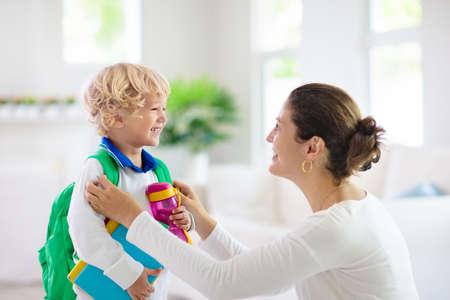 学校に戻る子供。母と子供は休暇の後に最初の学校の日の準備をしています。幼稚園や幼稚園に行く小さな男の子とママ。学生の梱包本、リンゴ、ランチをバックパックに入れて。