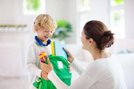 Bambino che torna a scuola. Madre e figlio si preparano per il primo giorno di scuola dopo le vacanze. Ragazzino e mamma che vanno all'asilo o all'asilo. Studente che imballa libri, mela e pranzo nello zaino.