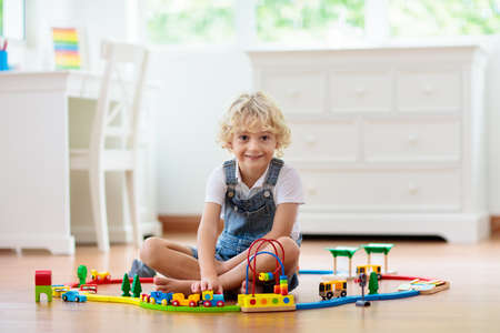 Kids play with wooden railway. Child with toy train. Educational toys for young children. Little boy building railroad tracks on white floor at home or kindergarten. Cute kid playing cars and engine.