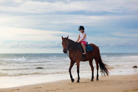 Kids riding horse on beach. Children ride horses. Cute little girl on pony on a ranch. Child and animal. Kid in safe helmet for horseback class. Travel with young child. Vacation on ocean shore.
