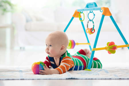 Cute baby boy on colorful playmat and gym, playing with hanging rattle toys. Kids activity and play center for early infant development. Newborn child kicking and grabbing toy in white sunny nursery Stock Photo