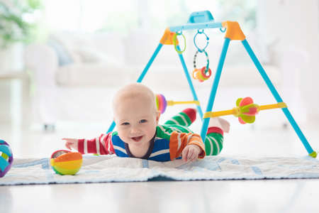 Cute baby boy on colorful playmat and gym, playing with hanging rattle toys. Kids activity and play center for early infant development. Newborn child kicking and grabbing toy in white sunny nursery