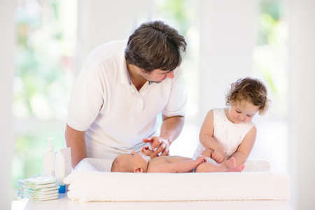 Father changing diaper to baby boy. Little girl helping dad to change nappy of newborn brother. Family in kids bedroom. Parent taking care of infant. Kid on dressing table on towel after bath.