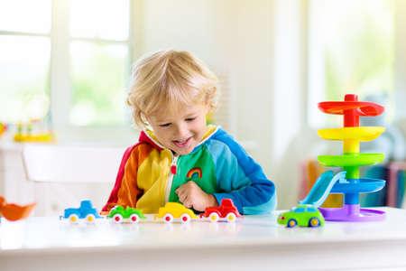 Niño jugando coches de juguete. Niño con coloridos vehículos educativos y juguetes de transporte. Niño conduciendo el coche al garaje de estacionamiento arco iris. Niños en casa o guardería. Juego de jardín de infantes o preescolar. Foto de archivo