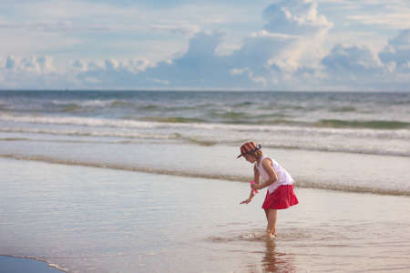 Child playing on tropical beach. Little girl wearing cowboy hat at seashore. Family summer vacation. Kid searching for shells. Water and sand fun for children. Kids play on ocean coast 写真素材