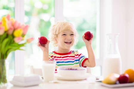 Niño desayunando. Niño bebiendo leche y comiendo cereales con frutas. Niño en la mesa de comedor blanca en la cocina en la ventana. Los niños comen en una mañana soleada. Nutrición sana y equilibrada para niños pequeños. Foto de archivo