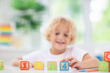 Child learning letters and numbers. Kid with colorful wooden abc blocks. Little boy spelling words with educational block toys. Kids doing school homework at white desk. Bedroom for preschool children Stockfoto