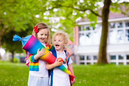 Child going to school. Boy and girl holding traditional candy cone on the first school day. Little students with books excited to be back to school. Beginning of class in Germany with sweets for kids. Stockfoto