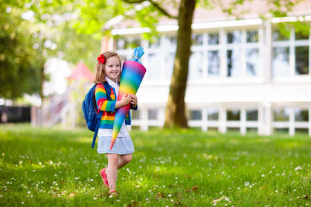 Happy child holding traditional German candy cone on the first school day. Little student with backpack and books excited to be back to school. Beginning of class in Germany with sweets for kids. Stockfoto