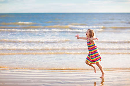 Child playing on tropical beach. Little girl at sea. Family summer vacation. Kids run, search for shells and play. Water and sand fun for children.