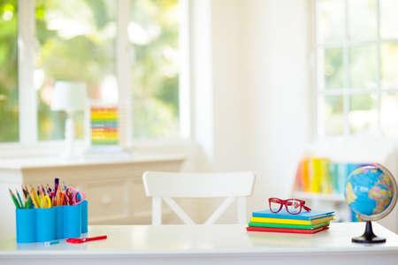 Powrót do szkoły. Sypialnia dziecięca z drewnianym biurkiem, książkami, globusem, plecakiem, okularami i ołówkami. Biały pokój z dużym oknem dla małego dziecka. Wnętrze domu dla dziewczynki lub chłopca. Stół do prac domowych i nauki.