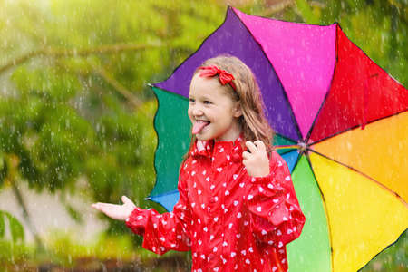 Kid playing in the rain in autumn park. Child with umbrella and rain boots play outdoors in heavy rain. Little girl in red jacket under fall shower. Kids fun by rainy weather. Children play in storm. Reklamní fotografie