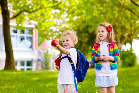 Dziecko idzie do szkoły. Chłopiec i dziewczynka trzymając książki i ołówki na pierwszy dzień w szkole. Mali uczniowie podekscytowani powrotem do szkoły. Początek zajęć po wakacjach. Dzieci jedzące jabłko na szkolnym podwórku