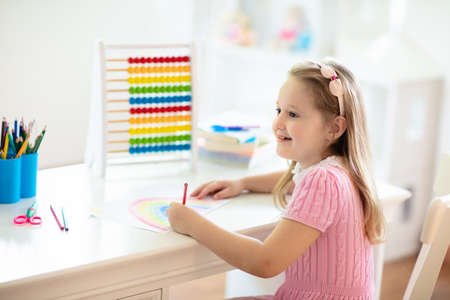 Child drawing rainbow. Kid painting at home. Little girl doing homework after school. Kids desk with abacus in white sunny bedroom. Children study, learn to read and write. Bedroom for young student. Reklamní fotografie