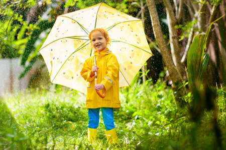 Child playing in the rain on sunny autumn day. Kid under heavy shower with yellow duck umbrella. Little boy with duckling waterproof shoes. Rubber wellies boots. Fall outdoor activity by rainy weather Reklamní fotografie