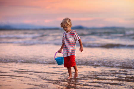 Child playing on ocean beach. Kid jumping in the waves at sunset. Sea vacation for family with kids. Little boy running on tropical beach of exotic island during summer holiday.