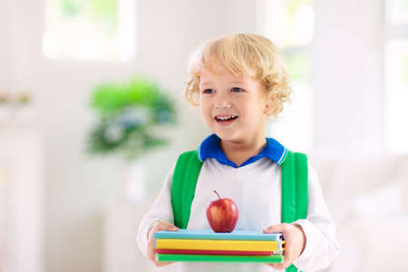 Child going back to school. Kid getting ready for first school day after vacation. Little boy on his way to kindergarten or preschool. Student packing books, apple and lunch in backpack. Reklamní fotografie